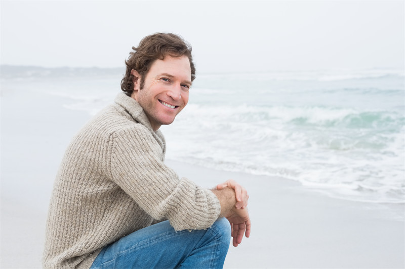 Side view portrait of a smiling casual young man relaxing at the beach
